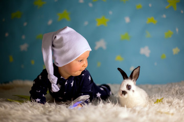 Little child, baby boy with cute white bunny and moon on a blue star and moon background
