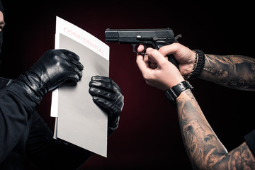 Man with gun protecting his confidential papers from robber