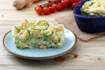 pasta gratinata maccheroni al forno con zucchini mandorle e formaggio su sfondo tavolo di cucina