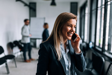 Portrait of a smiling blonde businesswoman talking on a phone during the break from a meeting.