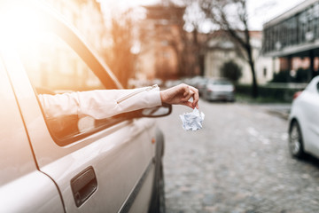 Close-up image of female hand throwing waste out of car window.