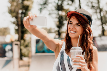 Portrait of cheerful young woman  smiling while taking selfie on her phone.