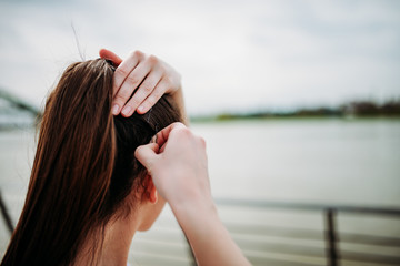 Girl putting bobby pins in hair outdoors. Close-up.