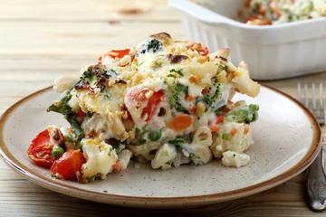pasta gratinata maccheroni al forno con verdure e legumi vari su sfondo tavolo di cucina