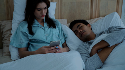Young woman playing phone while husband sleep nearby