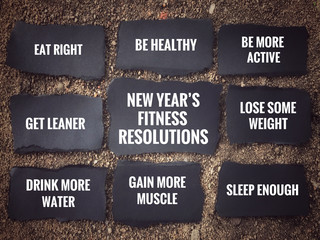 New Year's fitness resolutions concept - 'New Year's fitness resolutions' and its lists written on black pieces of papers. With vintage-styled background.