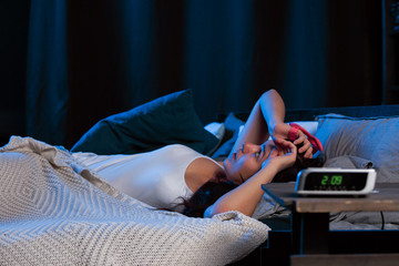 Portrait of young woman with insomnia lying on bed next to clock