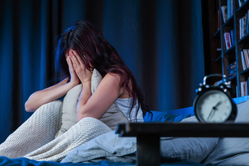 Image of unhappy woman with insomnia sitting on bed next to alarm clock