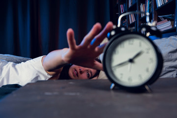 Image of dissatisfied woman with insomnia stretching arm to alarm clock at night
