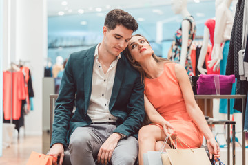 Woman and men being tired from shopping fashion leaning on each other