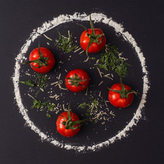 Tomatoes and flour on a black background