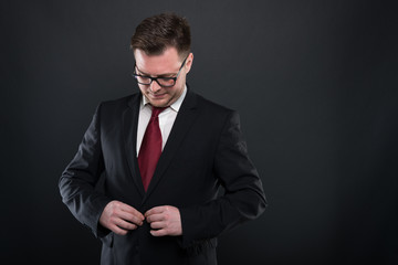 Portrait of business man wearing black suit buttoning jacket.