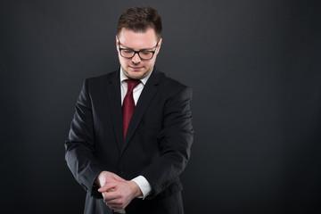 Portrait of business man wearing black suit arranging sleeve.