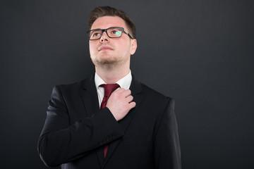 Portrait of business man wearing black suit arranging shirt.