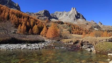 Fotomurales - A river flowing in an autumn colored mountain landscape. Vallee de la Claree, Nevache, France.