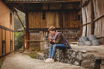 Tourist woman watches her pictures on holiday in a wooden village