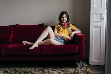 Woman with headphones on sofa