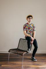Young stylish man posing at white wall