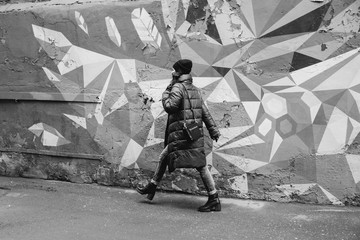 girl walking along the colorful wall, street photo