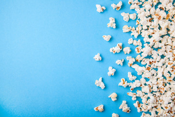 Popcorn scattered on blue background. Copy space for text Fototapete