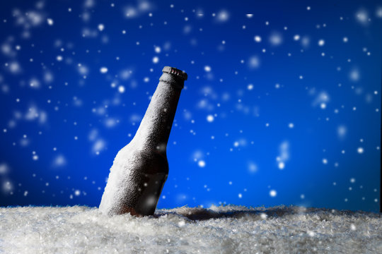 Cold beer bottle frozen in the ice with falling snow on blue moonlight background.