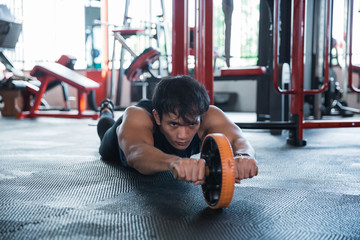 Front look man using abdominal roller