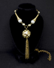 Gold pearl round surreal necklace with chain on black background