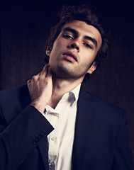 Handsome sexy male model posing in fashion suit and white style shirt looking on dark shadow background. Closeup toned portrait
