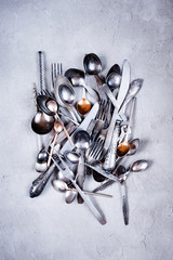 Vintage silverware scattered on the textured table