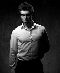 Charismatic sexy male model posing in white style shirt and looking serious on dark shadow background. Black and white portrait