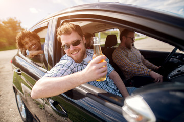 Charming multicultural friends having car road trip with open window and beer.