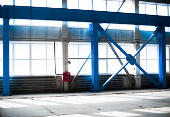 Manufacturing factory. Empty hangar building. Blue toned background. The production room with large windows and metal structures