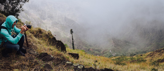 Panoramic shot of traveler making photo of amazing steep mountainous terrain with lush canyon valley on the path from Xo-Xo Valley. Santo Antao Island, Cape Verde