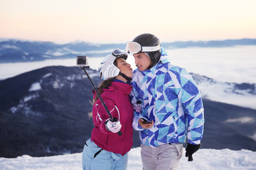 Couple taking selfie at snowy ski resort. Winter vacation