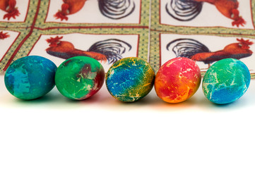 Five painted Easter eggs laid in one row against a paper napkin with a rooster.