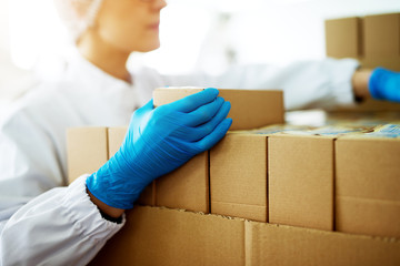 Close up of young focused female worker in sterile cloths is folding boxes on stacks of boxes in factory storage room.