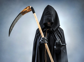 Grim Reaper inviting to come with him. Photo of personification of death wielding a large scythe in silhouette.