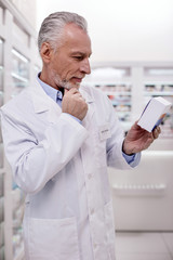 Be attentive. Mature thoughtful male pharmacist touching chin while holding medication