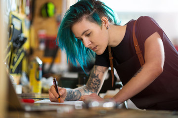 Confident young woman working in workshop