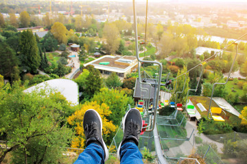 The legs of the passenger and the view down to the ground. Cable car in the summer park. Open seats for transportation of tourists