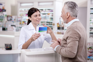 Effective medicine. Optimistic female pharmacist talking to mature man about side effect while carrying medication