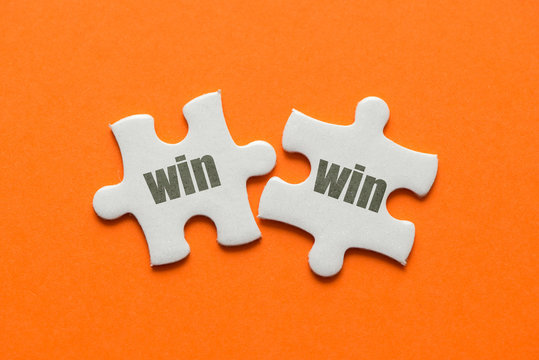 The word win win on two matching puzzle on orange background