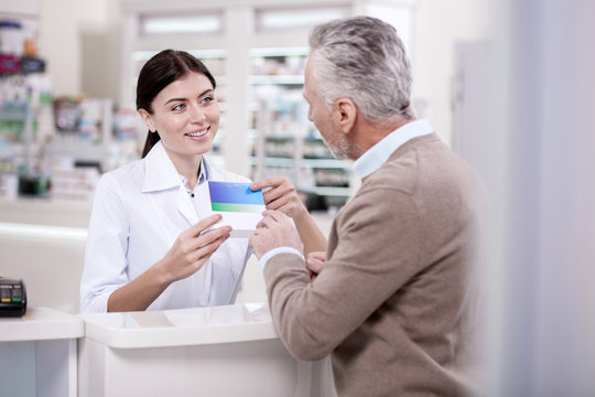 Safe medicine. Happy female pharmacist advising mature man about drug while carrying medication