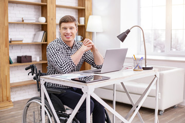 Disabled person. Cheerful male sitting on his wheelchair and holding hands together while leaning on table