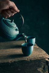Teapot and cup of tea on wooden background