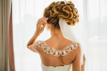 Beautiful yong woman in white wedding dress, back view