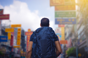 rear view of a backpacker looking at Chinatown road in Bangkok in morning , Thailand , Southeast asia . .