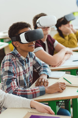 Multiethnic high school students using virtual reality headsets in classroom