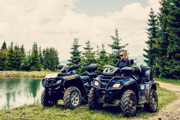 Fototapeta Excited young woman on quad bike. Happy young woman driving all terrain vehicle in nature.