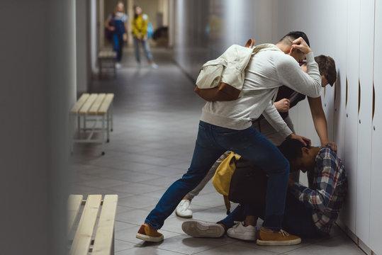 frightened african american schoolboy being bullied in school corridor